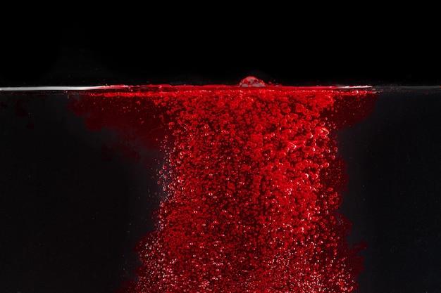 Rode bruisende waterplons in een pool tegen zwarte achtergrond
