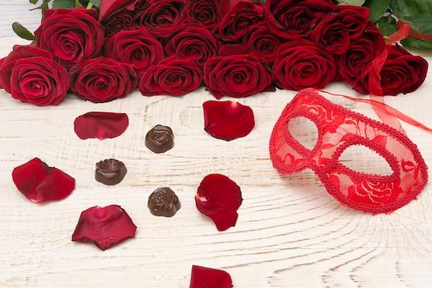 Rode carnaval masker, boeket van rode rozen en chocolade op licht houten.