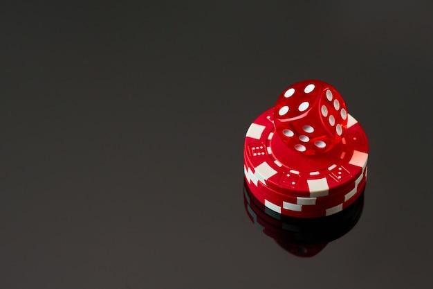Rode casino dobbelstenen en chips geïsoleerd over zwarte reflecterende achtergrond