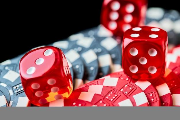Rode casino dobbelstenen en chips op zwarte tafel