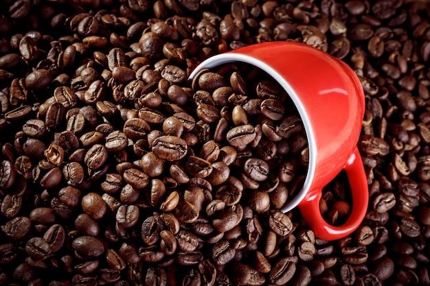 Rode ceramische koffiekop die in de hete koffiebonen ligt.