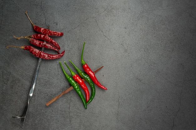 Rode chili heeft een spies op zwart.