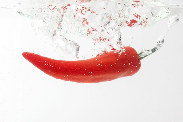 Rode chili peper vallen in water