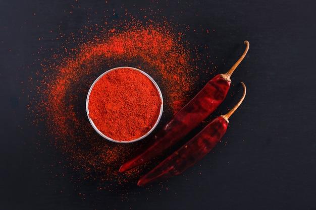 Rode chili peper vlokken en chili poeder barsten op zwarte achtergrond