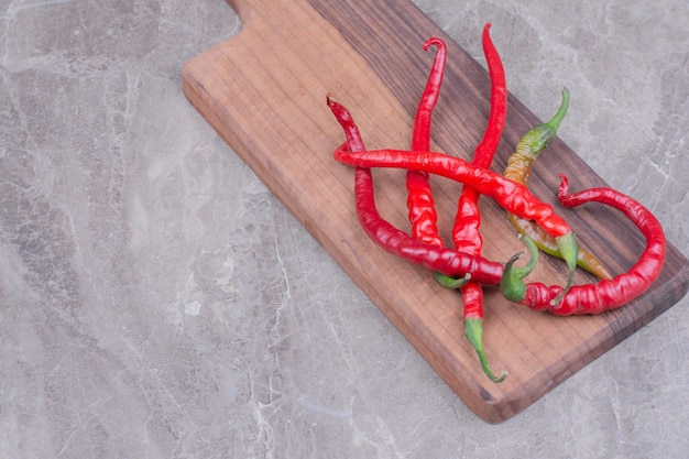Rode chili pepers geïsoleerd op een houten schotel op marmeren oppervlak