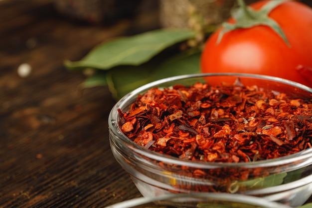 Rode chili specerij in glazen kom met kruiden op donkere tafel