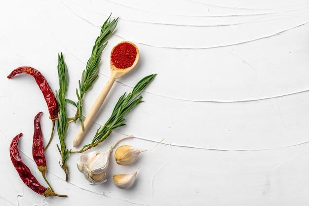 Rode chilipepers en andere kruiden op wit met kopie ruimte, plat leggen
