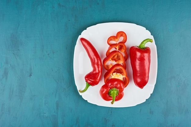 Rode chilipepers in een witte plaat.