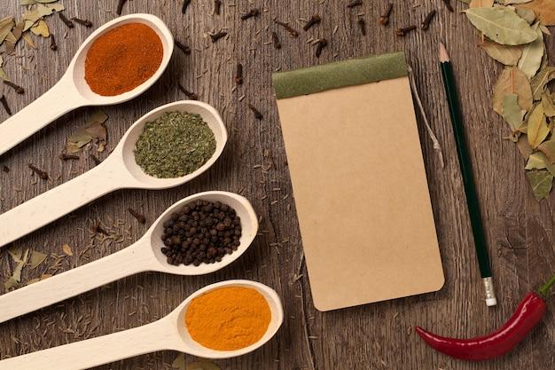 Rode chilipepers, kruiden in lepels, notitieboekjedocument en potlood op eikenhouttextuur