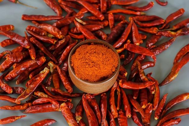 Rode chilipoeder of paprika in een houten kom op een donkere achtergrond, close-up. koken ingrediënten, smaak.