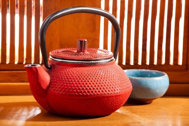 Rode chinese theepot met een kom op de achtergrond van een houten raam met zonnestralen. thee ceremonie