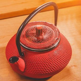 Rode chinese theepot op een achtergrond van een houten raam met zonnestralen. thee ceremonie