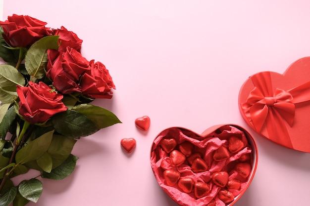 Rode chocoladesnoepjes en rozen op roze voor valentijnsdag. wenskaart met kopie ruimte.