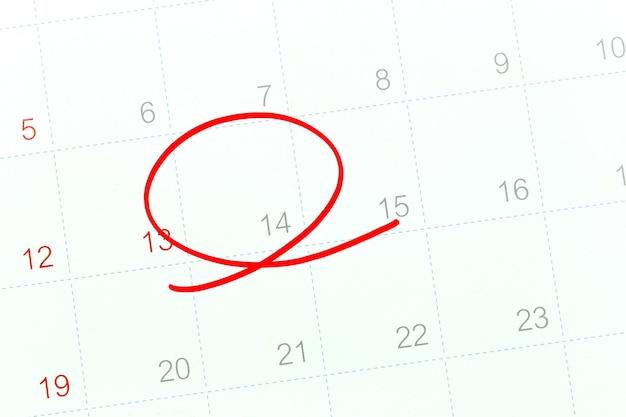 Rode cirkel van de pen op het kalenderpapier toont de 14e voor ontwerp in valentijnsdag concept.