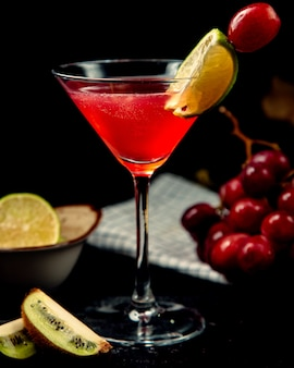 Rode cocktail op tafel met schijfje citroen