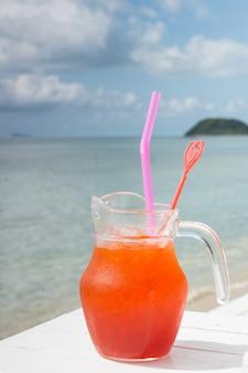 Rode cocktail op witte lijst die over oceaan wordt geplaatst