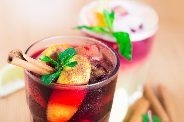 Rode cocktails met munt, ijs en kaneel sluiten omhoog bij een bar