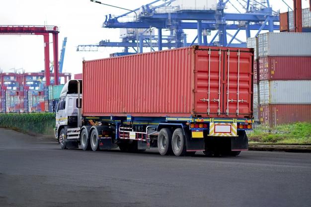 Rode containervrachtwagen in scheepshaven logistiek. transportindustrie in havenbedrijven. import, export logistieke industrie