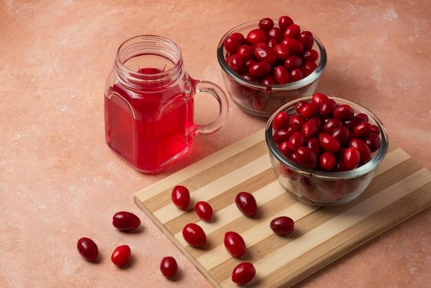 Rode cornels in glazen beker met sap in de pot.
