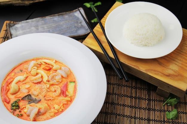 Rode curry met garnalen op een witte plaat, rijst en eetstokjes