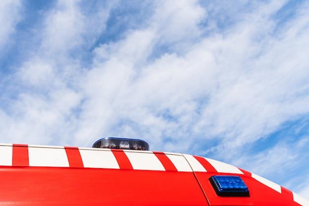 Rode dak van een medische ambulance over blauwe hemel met wolken