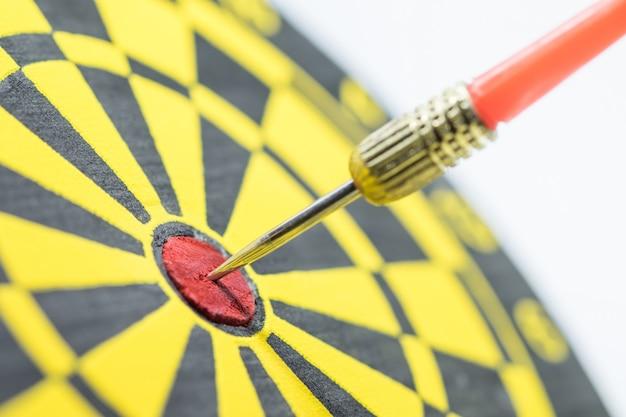 Rode dartpijl die in het doelcentrum van dartboard raakt.