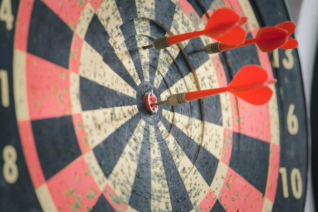 Rode dartpijl die op het oude dartbord is geraakt