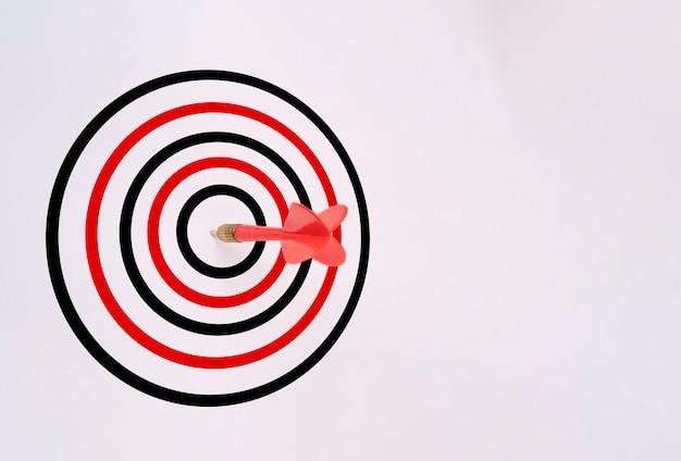 Rode dartpijl geraakt op doelbord dat op wit wordt geïsoleerd