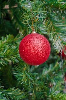 Rode de baldecoratie van de kerstboom, met groene boom