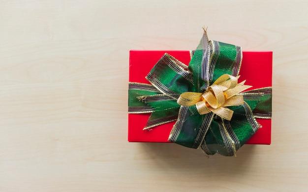Rode de giftdoos van kerstmis die op een houten vloer wordt geplaatst.