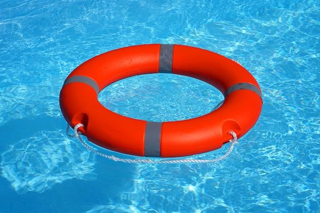 Rode de ringvlotter van de reddingsboeipool op blauw water. reddingsring die bovenop zonnig blauw water drijven. reddingsring in zwembad