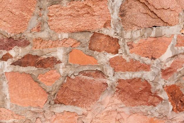 Rode de textuur en de achtergrond van de steenmuurberg
