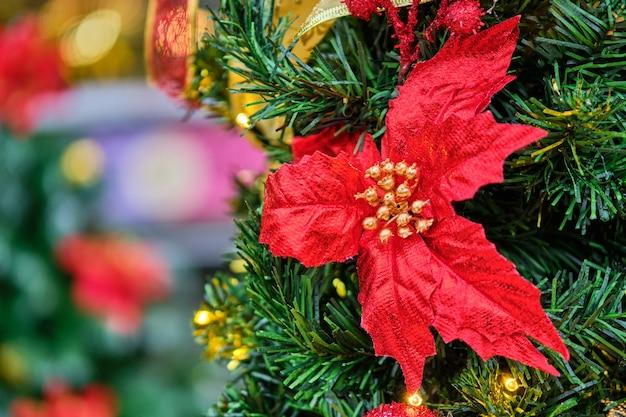 Rode decoratie in de vorm van een bloem op een kerstboom