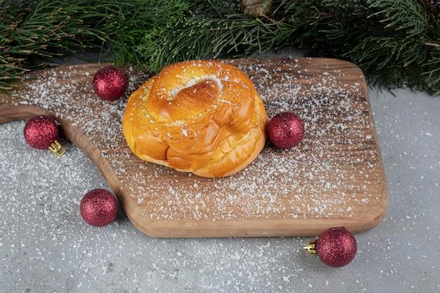 Rode decoratieve kerstballen, dennentakken en een klein broodje op marmeren tafel.