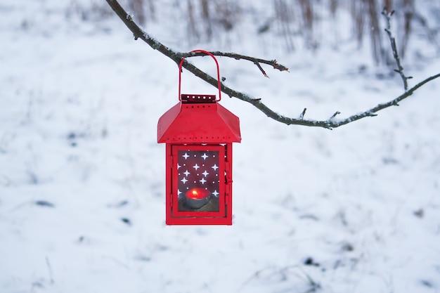 Rode decoratieve lantaarn met kaars die aan de boomtak hangt besneeuwde winteravond in het park