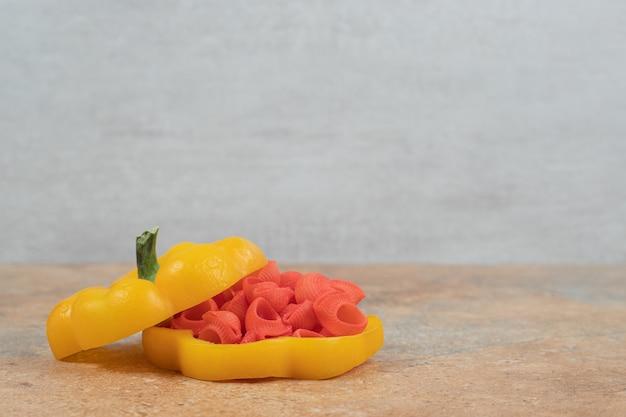 Rode deegwaren in paprika op oranje achtergrond