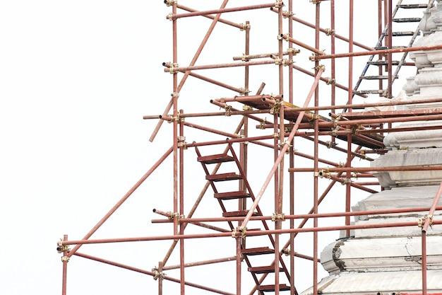 Rode die steiger bij de bouwwerf op witte achtergrond wordt geïsoleerd