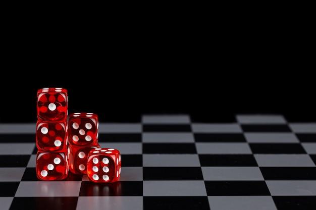 Rode dobbelstenen op een schaakbord op een zwarte achtergrond