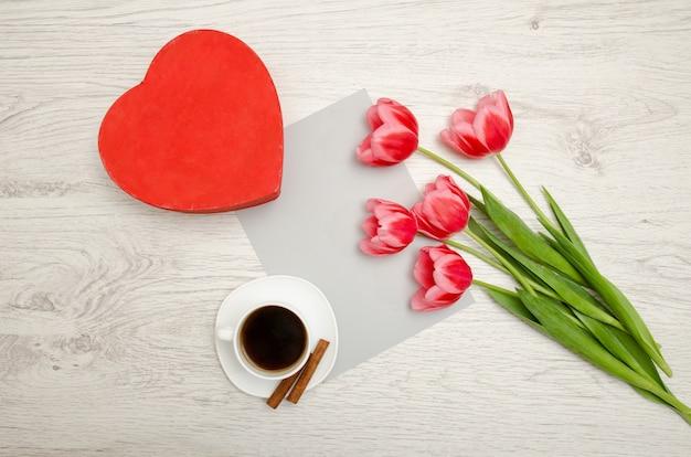 Rode doos in hartvormige, roze tulpen, grijs blad en een koffiemok