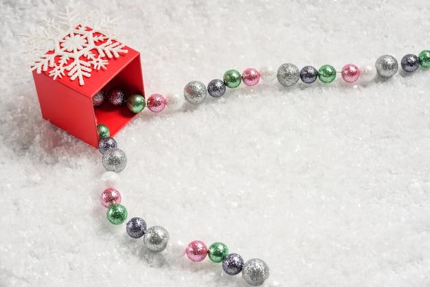 Rode doos met een sneeuwvlok en een kerstboomkrans in de sneeuw.