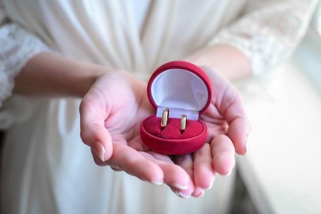 Rode doos met gouden trouwringen in de handen van de bruidclose-up