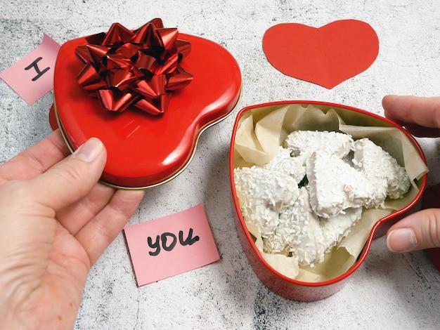 Rode doos met hart met strik in handen met cakes, zoete valentijnsdag, close-up