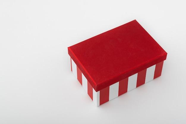 Rode doos met strepen op witte achtergrond. cadeaupapier. sjabloon. kopieer ruimte.