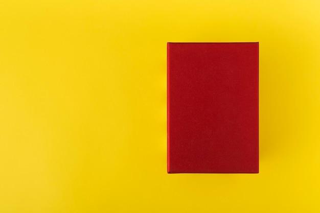 Rode doos op gele achtergrond bovenaanzicht. rode rechthoek op een gele achtergrond. kopieer ruimte. bespotten