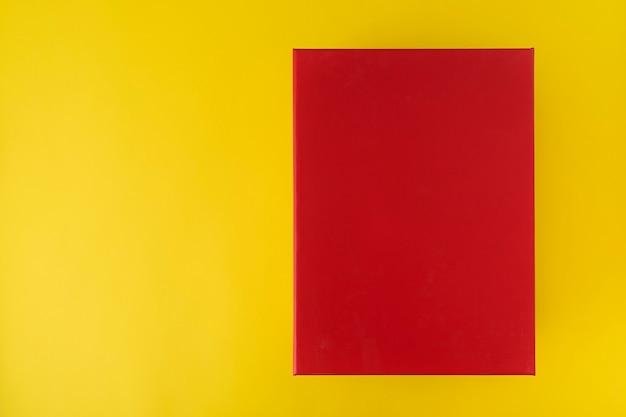Rode doos op gele achtergrond, bovenaanzicht. rode rechthoek.