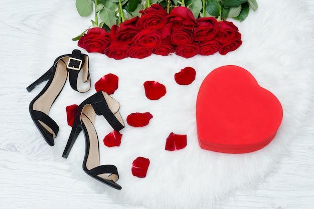 Rode dozen in hartvorm, zwarte schoenen en een boeket rode rozen op een witte vacht