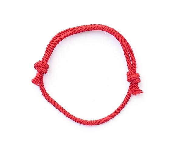 Rode draad string als amilet voor pols geïsoleerd op wit rode braslet met knopen bovenaanzicht