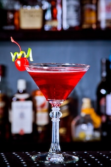 Rode drankcocktail met kersen in martiniglas, kersen en limoenschil aan de toog