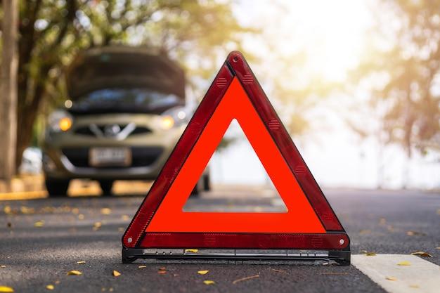 Rode driehoek, rood noodstopbord, rood noodsymbool en autostop en parkeren op de weg.