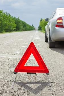 Rode driehoek van een auto op de weg. pech van de auto bij slecht weer